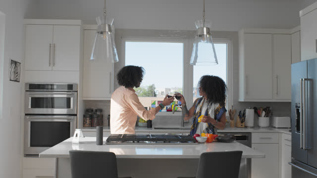 vídeos de stock e filmes b-roll de cheerful couple prepare food while listening to music in their kitchen - on the move