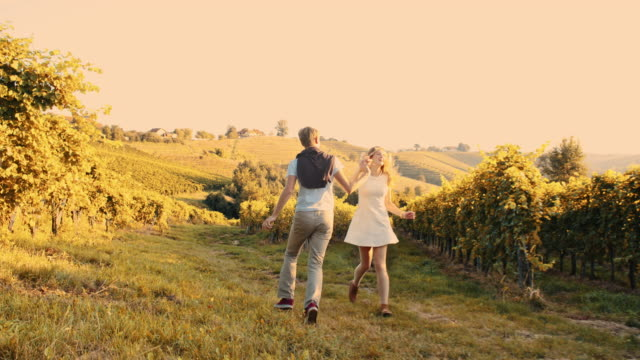 Cheerful couple running in the vineyard