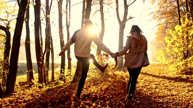 SLO MO Cheerful couple running through autumn forest