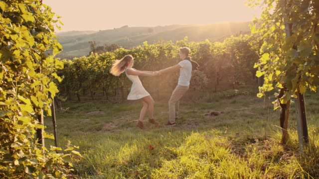 SLO MO Cheerful couple spinning in the vineyard