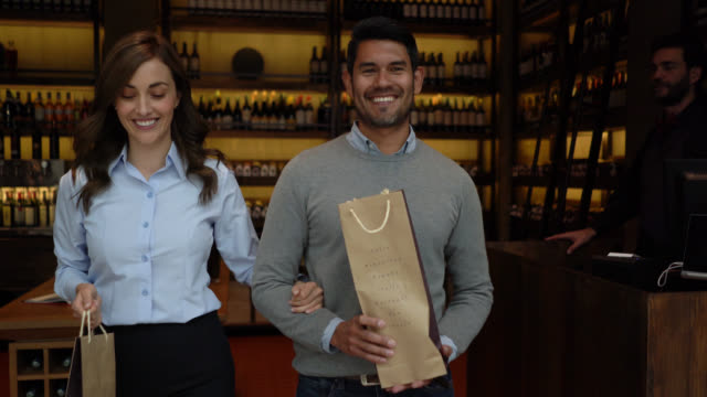 cheerful couple walking out and talking after purchasing wine bottles at a wine cellar - paper bag stock videos & royalty-free footage