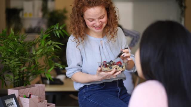 stockvideo's en b-roll-footage met vrolijk krullend harige vrouw met ontbijt op het werk - gezonde voeding