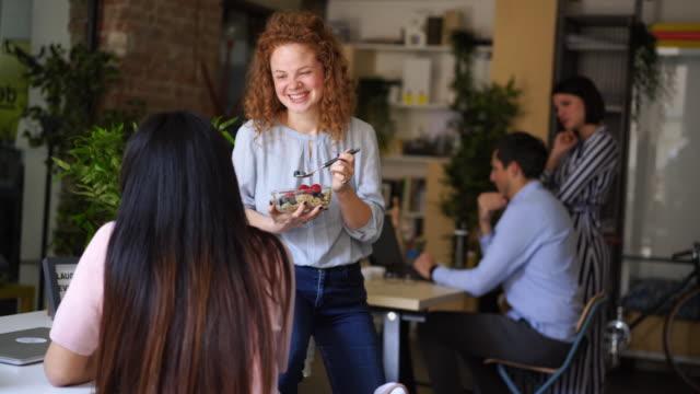 vidéos et rushes de femme curly-haired gai ayant le petit déjeuner au travail - blog
