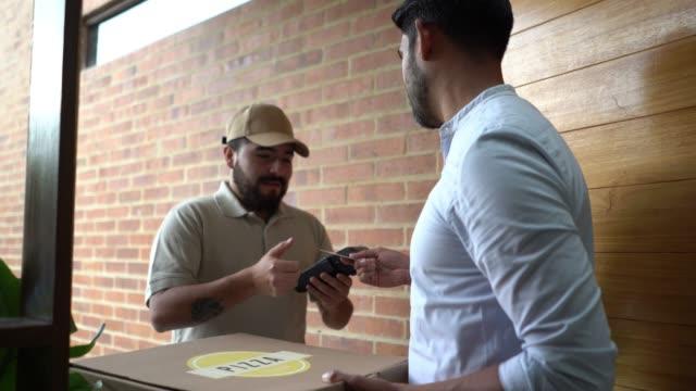 vídeos de stock, filmes e b-roll de homem de entrega alegre entregando a ordem da pizza ao cliente quando pagar com cartão de crédito - entregando