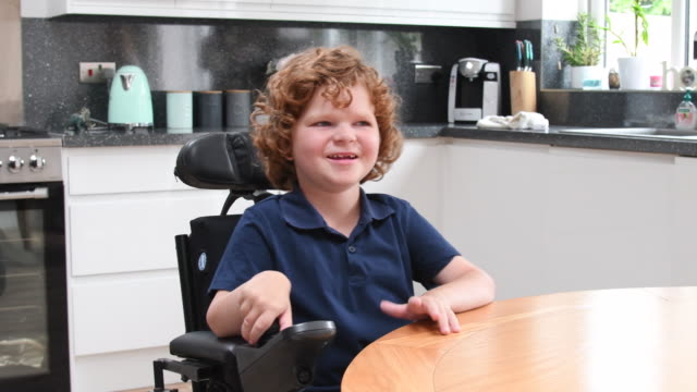cheerful disabled boy leaving kitchen in wheelchair and smiling - self sufficiency stock videos and b-roll footage