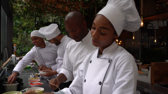 cheerful diverse team of chefs talking and smiling while preparing food at the restaurant - chef stock videos & royalty-free footage