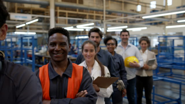 cheerful diverse team of engineers, blue collar workers, quality inspectors, manager standing in a row smiling at camera - line stock videos & royalty-free footage