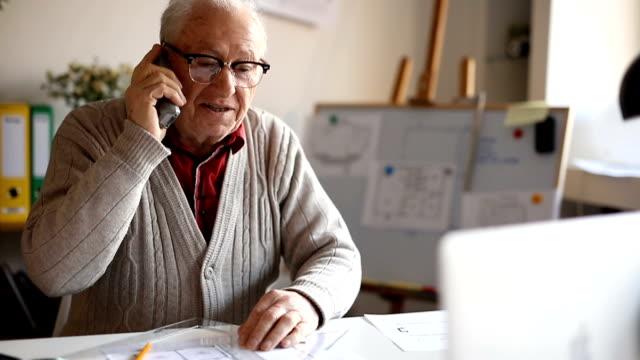 Cheerful elderly man talking on the phone