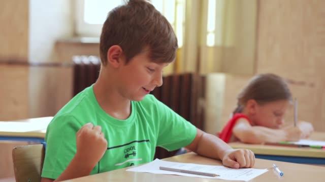 fröhlicher grundschüler jubelt über die richtige antwort auf eine pädagogische prüfung in der schule - schulische prüfung stock-videos und b-roll-filmmaterial