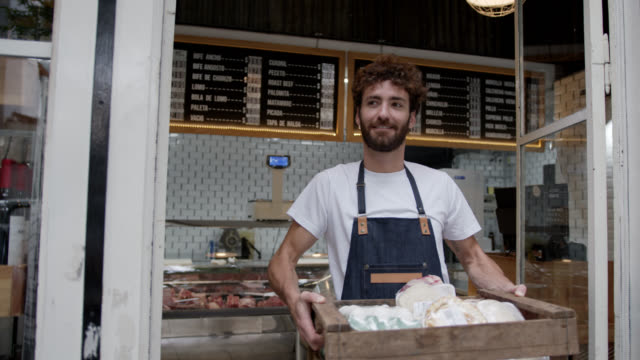 cheerful employee of the deli leaving with a wood box with meat, eggs and other products for a delivery smiling - apron stock videos & royalty-free footage