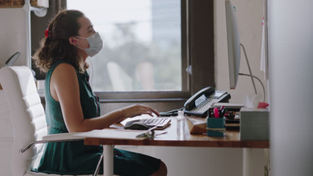 cheerful employee wearing protective face mask works at computer in office while listening to music, thanks coworker who sets clipboard on desk - computertastatur stock-videos und b-roll-filmmaterial