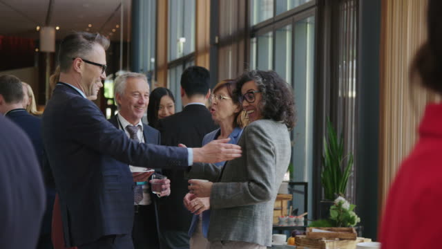 cheerful entrepreneurs shaking hands during break - business conference stock videos & royalty-free footage