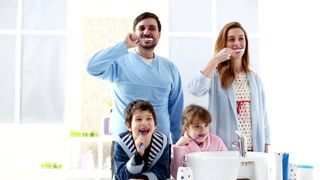 hd: cheerful family brushing teeth together. - borsta tänder bildbanksvideor och videomaterial från bakom kulisserna