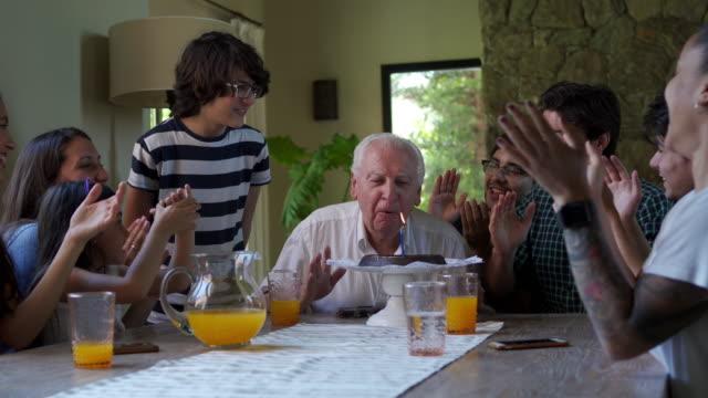 vídeos de stock e filmes b-roll de cheerful family celebrating grandfather's birthday - família de várias gerações