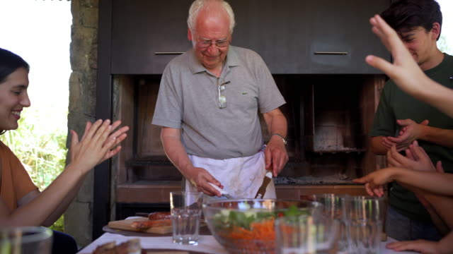 vidéos et rushes de applaudissements joyeux de famille pour un chef grand-père - féliciter