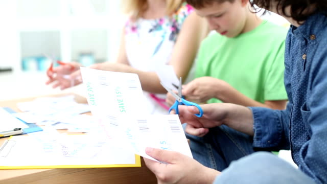 hd: cheerful family cutting shopping coupons. - scissors stock videos & royalty-free footage