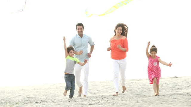 ws cheerful family flying kites on beach / india - vier personen stock-videos und b-roll-filmmaterial