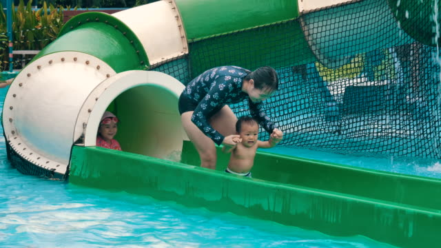 cheerful family having fun sliding a slider in water park - 6 11 months stock videos & royalty-free footage