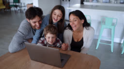 Cheerful family of four watching a funny movie on laptop at home