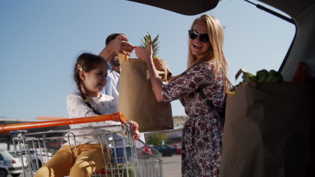 cheerful family packing groceries in car trunk - shopping bags stock videos & royalty-free footage