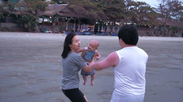 glad familj lekfullt med pojke (6-11 månader) på stranden - 6 11 månader bildbanksvideor och videomaterial från bakom kulisserna