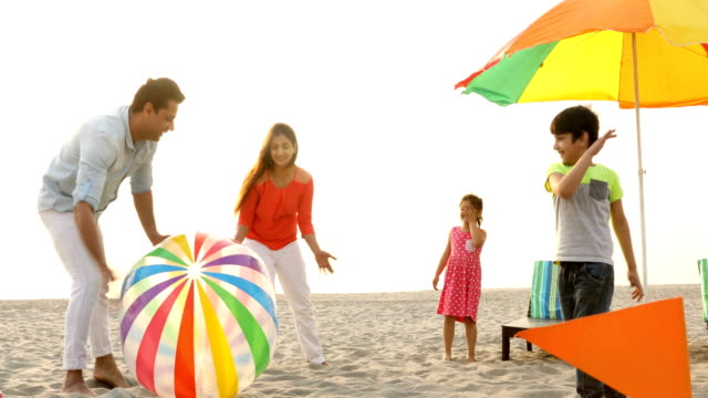 WS Cheerful family playing with ball on beach / India