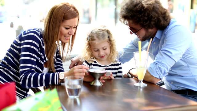 HD: Fröhliche Familie sitzen In einem Restaurant im Freien.