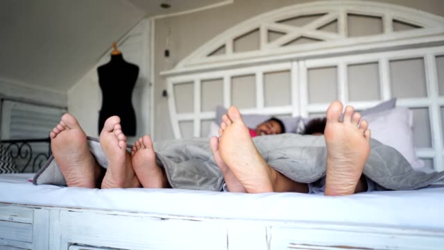 cheerful family spending the morning in bed - kids feet tickle stock videos & royalty-free footage