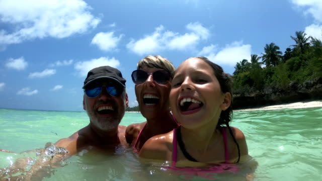 cheerful family spinning in the sea on tropical vacations - vacations stock videos & royalty-free footage