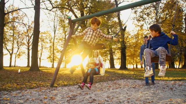 slo mo cheerful family swinging in the park - swinging stock videos & royalty-free footage