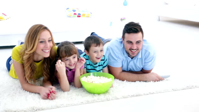 stockvideo's en b-roll-footage met hd: cheerful family watching tv together. - op de buik liggen