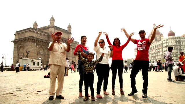 Cheerful family with raised arms having fun at the Gateway Of India, Mumbai