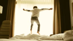 Cheerful fashion dressed boy active jumping on the bed in the morning