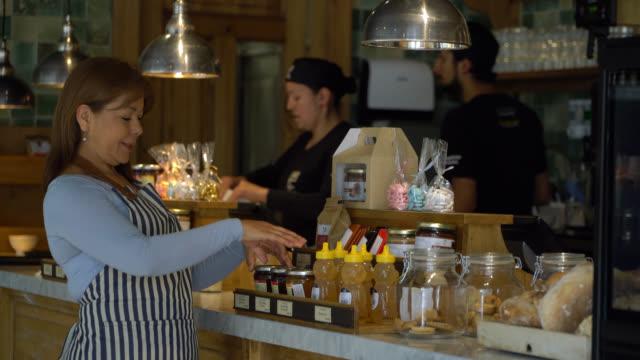 vídeos de stock, filmes e b-roll de alegre dono de negócios do sexo feminino de uma padaria organizando a exibição de balcão com produtos deliciosos - arranjo