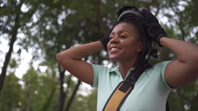 cheerful female courier black ethnicity taking off her cycling helmet after she finished her job for today - cycling helmet stock videos & royalty-free footage