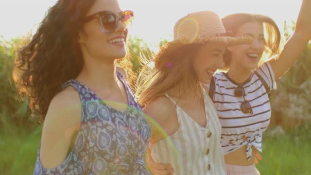 cheerful female friends walking among long grass - handbag stock videos & royalty-free footage