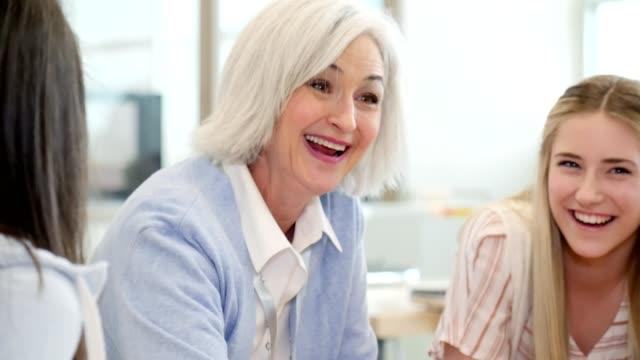 cheerful female high school teacher assists female teacher - studente di scuola secondaria allievo video stock e b–roll