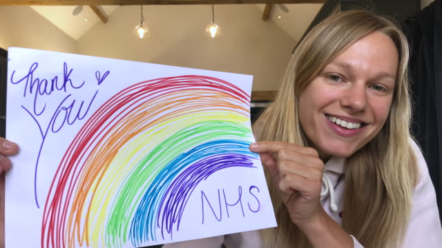cheerful female holding up rainbow drawing to thank healthcare workers during covid-19 pandemic, loo,img at camera - thank you englischer satz stock-videos und b-roll-filmmaterial