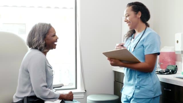 fröhliche krankenschwester im gespräch mit patientin - medizinerkleidung stock-videos und b-roll-filmmaterial