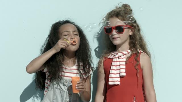 vídeos de stock, filmes e b-roll de cheerful friends blowing bubbles during summer - óculos escuros acessório ocular