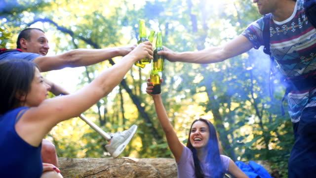 stockvideo's en b-roll-footage met vrolijke vrienden genieten van drankjes in het bos - minder validen