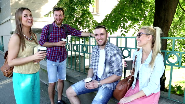 cheerful friends in the street drinking coffee - coffee drink stock videos & royalty-free footage