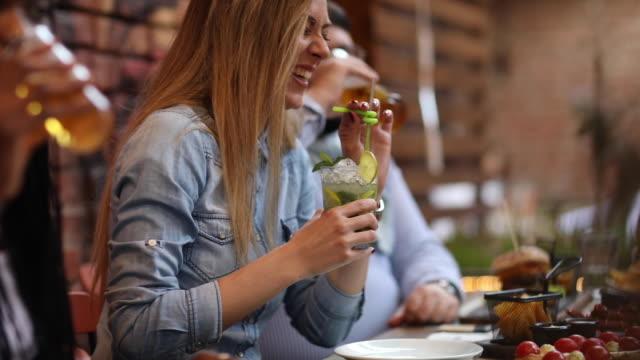 vídeos de stock, filmes e b-roll de amigos alegres rindo e curtindo o tempo juntos em restaurante ao ar livre - coquetel