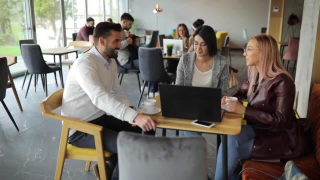カフェでノートパソコンを使用して陽気な友人 - 親睦会点の映像素材/bロール