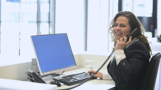 cheerful front desk lady doing her job with passion - administrator stock videos and b-roll footage
