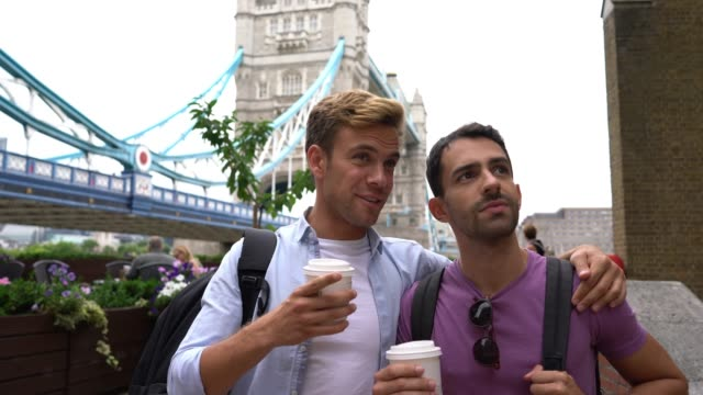 cheerful gay couple doing tourism at the london bridge while enjoying a coffee to go - riverbank stock videos & royalty-free footage