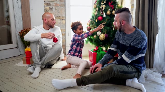 cheerful gay family decorating a christmas tree together - decorating the christmas tree stock videos & royalty-free footage