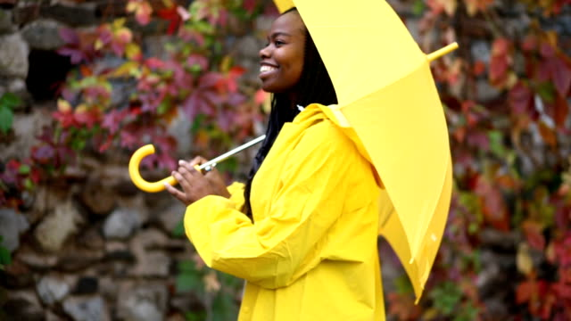 cheerful girl awaiting the rain - yellow stock videos & royalty-free footage