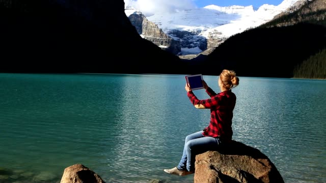 cheerful girl by the mountain lake using digital tablet - banff national park stock videos & royalty-free footage