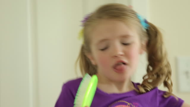 stockvideo's en b-roll-footage met cheerful girl dancing while singing at home - haar borstelen